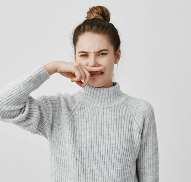 Displeased woman wearing casual closing nose with index finger looking with disgust. Young female blogger smelling something unpleasant while working in cafe. Bad smell concept